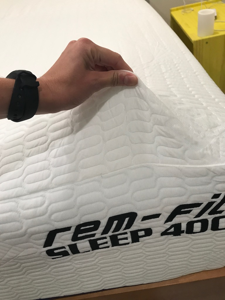 REM-Fit Sleep 400 Mattress Review was recently completed by the MattressJunkie.com team. REM-Fit is a division of Protect A Bed and has 35 years of sleep industry experience. The REM-Fit team believes in a restful sleep experience and has an array of sleep related products. REM-Fit was launched in 2014 as an active bedding brand that helps sleepers achieve a healthy and active lifestyle by getting the best sleep possible for maximum recovery and comfort. REM-Fit sent over a queen REM-Fit Mattress for this review. The REM-Fit Sleep 400 Mattress in queen retails for $1099.99 and is made of memory foam. We recently reviewed the REM-Fit Sleep 300 Mattress and were very pleased with it so read more on the REM-Fit Sleep 400 Mattress below. What's the REM-Fit Sleep 400 Mattress cover made of? REM-Fit Sleep 400 Mattress cover is made of Hi-Flow knit. The Re-Ax Unleased temperature regulating, moisture wicking cover has ventilated side mesh that keeps heat from building up under the sleeper's body. This nicely hugging cover is mostly white with purple accents. The cover is attractive and high quality. What's under the REM-Fit Sleep 400 Mattress cover? REM-Fit Sleep 400 Mattress is 12 inches in height and has 3 layers of foam. The first layer under the cover is 2 inches of cooling gel memory foam. The gel infused memory foam serves as a comfort layer while also serving as a temperature regulating layer that disperses heat from the sleeper's body. The second layer is 2.5 inches of response foam. Response foam provides support and comfort to the mattress. Response foam is great for multi-position and restless sleeper's. Response foam responds quickly to changes so sleeper's can achieve optimum support for multiple sleep styles. The last layer is 7.5 inches of support foam. High quality support foam is critical for the overall longevity of the mattress's lifespan and long term support. What type of sleep style works best for the REM-Fit Sleep 400 Mattress? The REM-Fit Sleep 400 Mattress is medium in terms of firmness. Medium mattresses work the best for back and side sleepers. Stomach sleepers usually prefer a firmer sleep surface. How much does the REM-Fit Sleep 400 Mattress cost? Twin- $749.99 Twin XL- $749.99 Full- $949.99 Queen- $1099.99 King- $1299.99 California King- $1299.99 What type of warranty does the REM-Fit Sleep 400 Mattress have? The REM-Fit Sleep 400 Mattress has a 25 year warranty. Most memory foam mattresses have a much shorter warranty period. REM-Fit Sleep 400 Mattress is made with high quality materials and built to last. The 25 year warranty is a direct testament to the quality of the mattress. What surface is best for the REM-Fit Sleep 400 Mattress? We reviewed our mattress on a platform bed. Any hard surface like a platform base, box spring, adjustable bed, or the floor would work great with the REM-Fit Sleep 400 Mattress. Do we recommend the REM-Fit Sleep 400 Mattress? We loved the REM-Fit Sleep 300 Mattress but the REM-Fit Sleep 400 Mattress is even better. The extra 2 inches in height is a big difference when comparing the two mattresses. REM-Fit Sleep 400 Mattress was just the right level of coolness and firmness for me. I am a side sleeper and side and back sleepers would like the REM-Fit Sleep 400 Mattress. REM-Fit also gives each purchaser an activity tracker so you can actually measure your daily activity and sleep. This is great for those who are wanting to actively make changes in their daily life. REM-Fit Sleep 400 Mattress is a great choice for side and back sleepers who want just the right level of comfort and cooling. REM-Fit really exceeded our expectations with the REM-Fit Sleep 400 Mattress. Learn more about the REM-Fit Sleep 400 Mattress here….